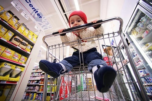Bố mẹ nên cẩn thận về vấn đề vệ sinh khi cho trẻ ngồi vào trong xe đẩy siêu thị. (Ảnh minh họa)